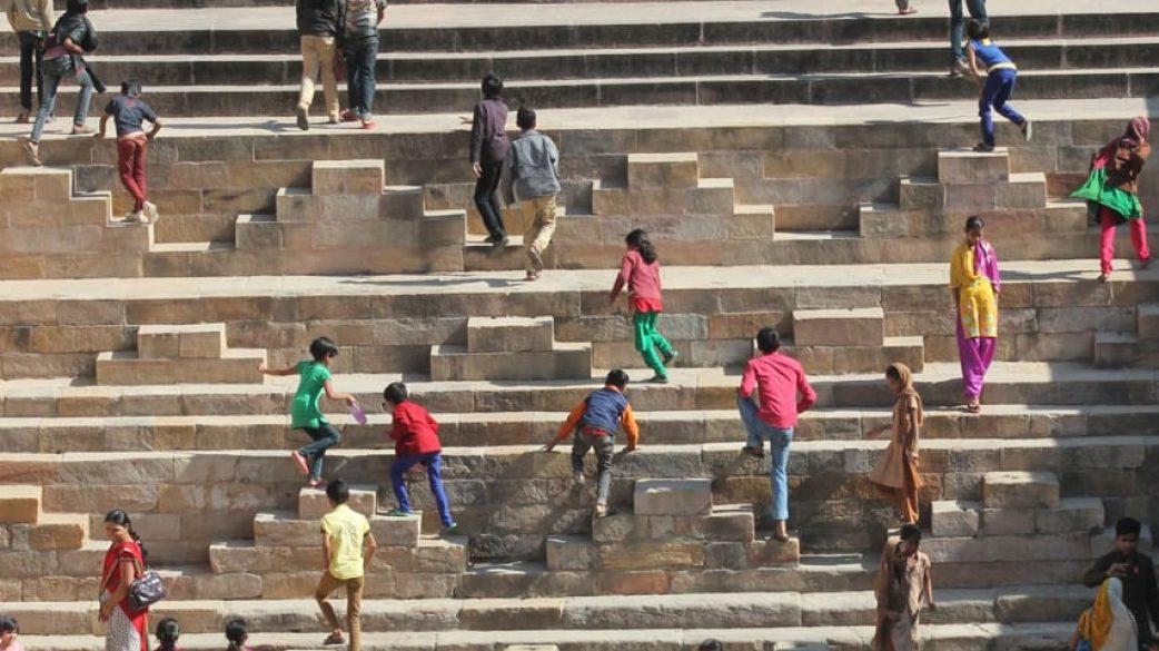 Children scramble up the Patan step well